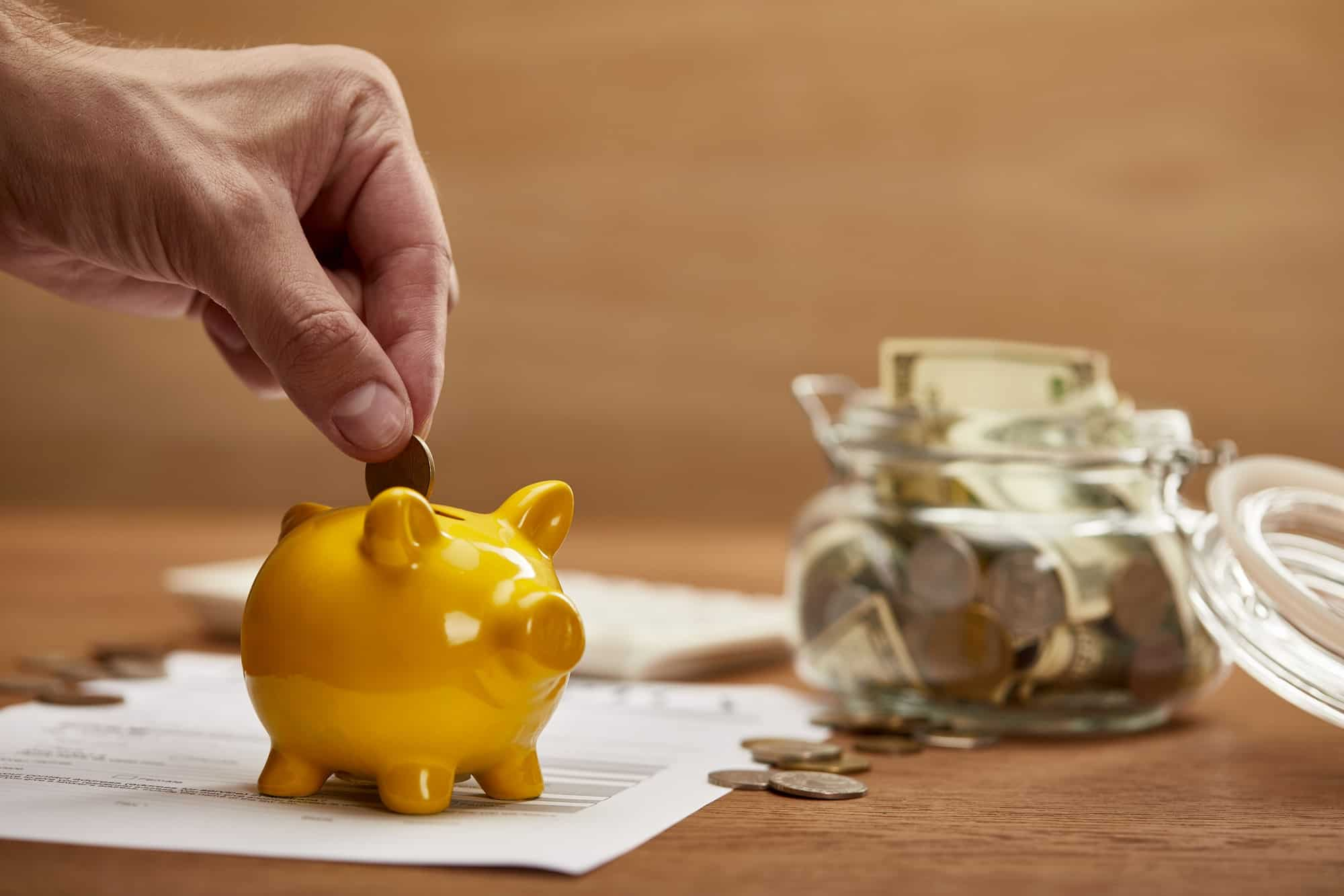 cropped view of man putting coin in yellow piggy bank